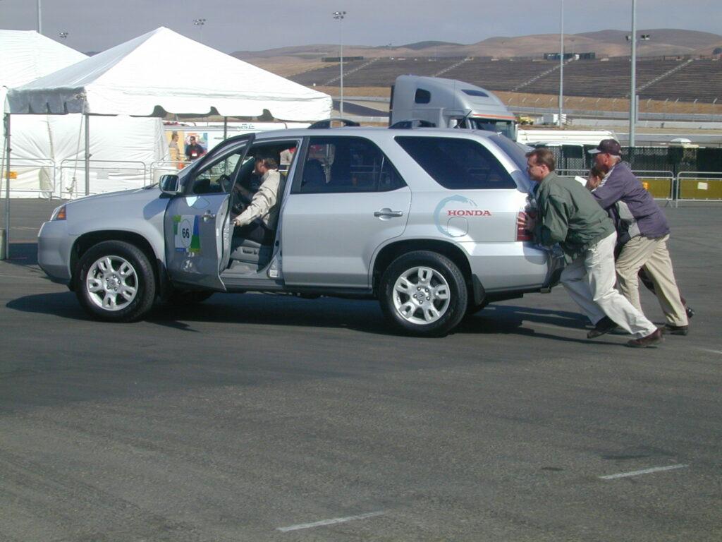 three pushing and one steering Honda's broken SUV