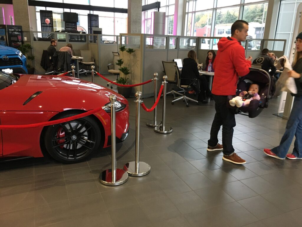 Red jacket dad holding baby in car seat in  auto dealer next to red car
